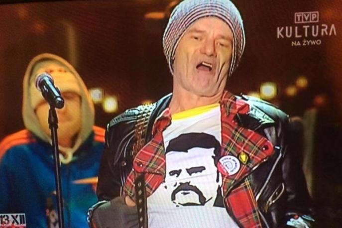Robert Brylewski w koszulce z Lechem Wałęsą podczas koncertu transmitowanego przez TVP